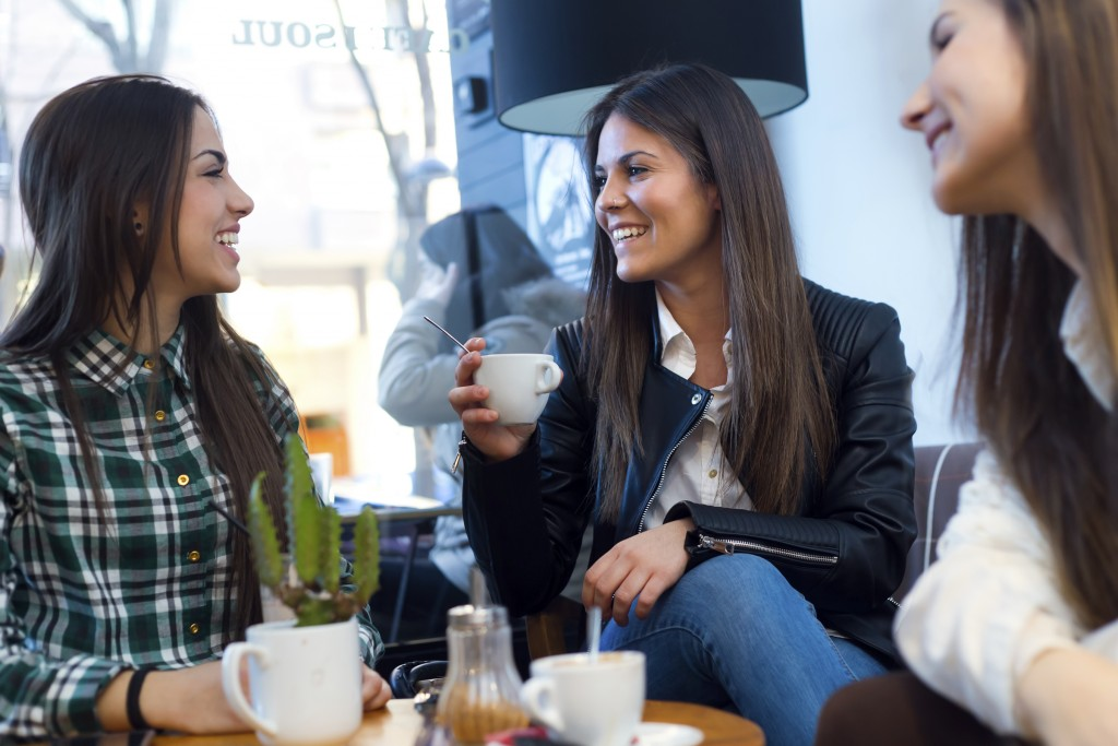 Portrait of three young woman drinking coffee and speaking at cafe shop.