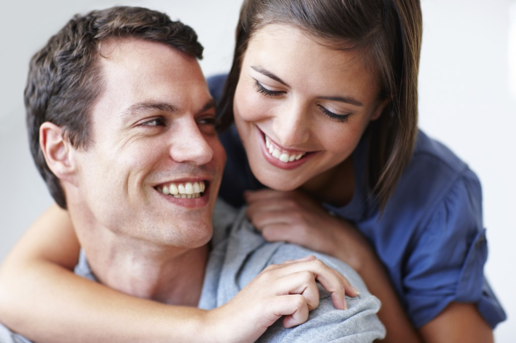 Close-up of a beautiful young couple laughing together, isolated on white