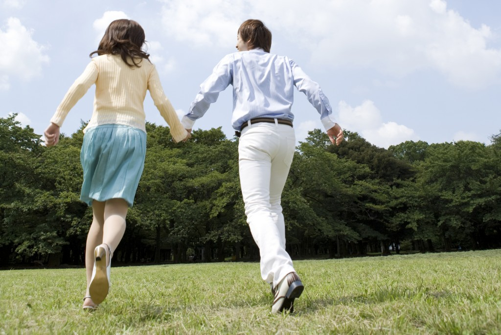 Couple holding hands run on lawn