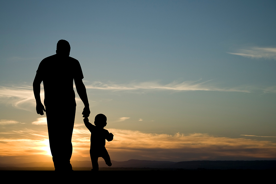 A man and his son walking at sunset