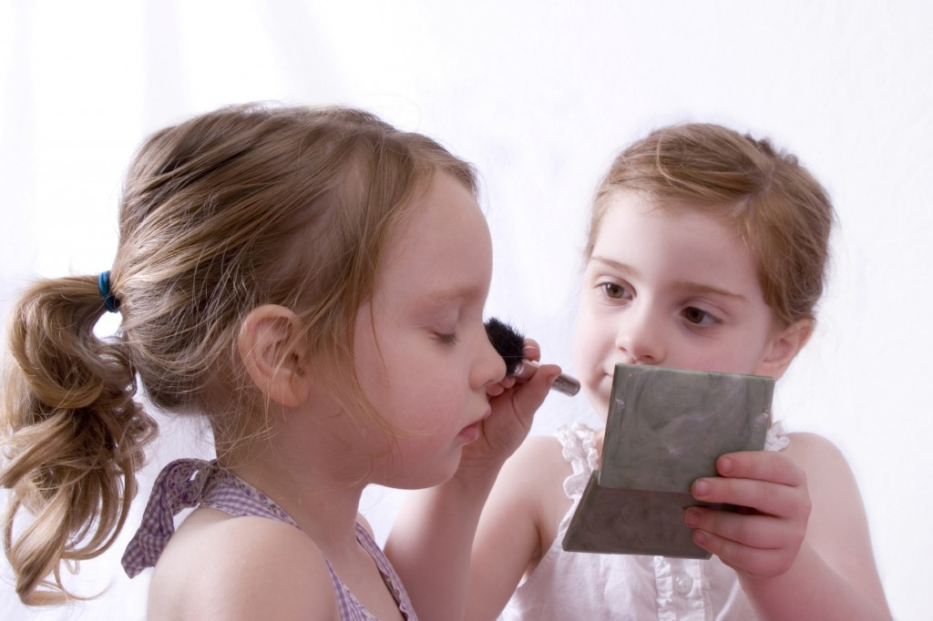 Cute little girls putting on makeup