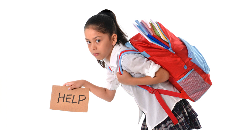 Network iStock license sweet little girl carrying very heavy backpack or schoolbag full of school notepads and textbooks causing her stress and pain on her back due to overweight isolated on white background