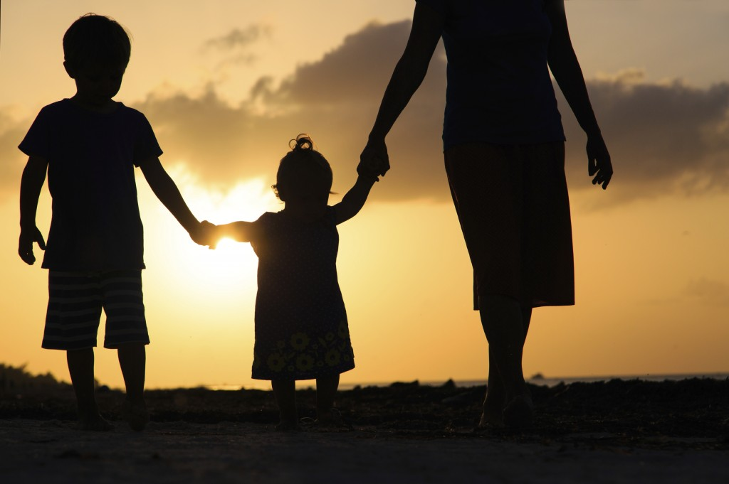 mother with kids walking on beach at sunset