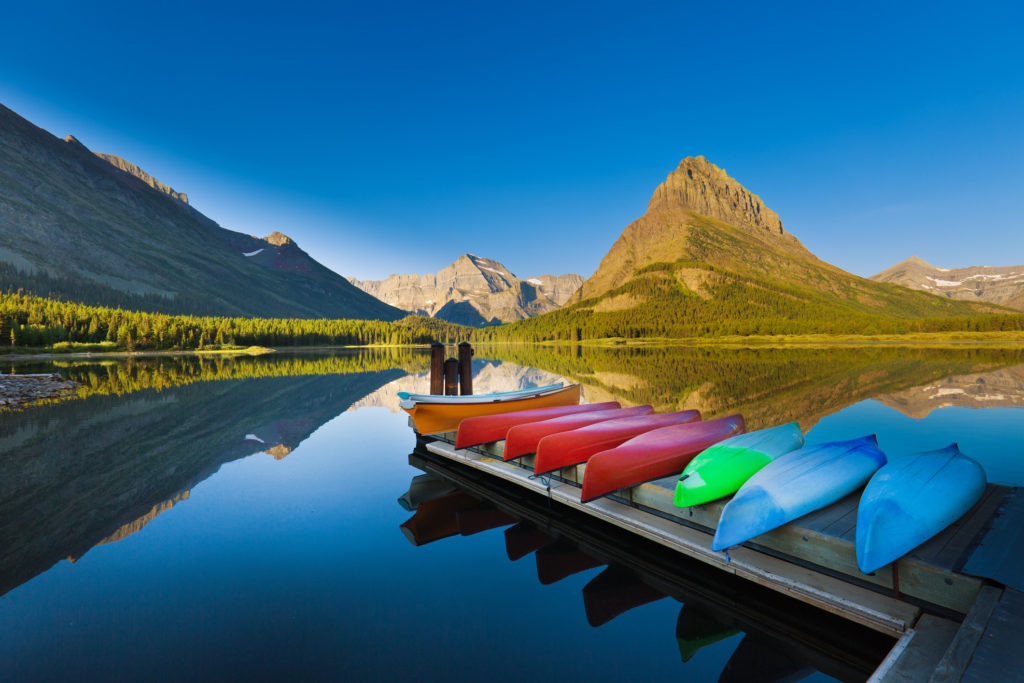 A group of canoes resting at the dock deck at Many Glacier Swiftcurrent Lake at Glacier National Park. Many Glacier National Park, Montana, a scenic tourist destination in the northwest region of United States. Photographed in horizontal format.