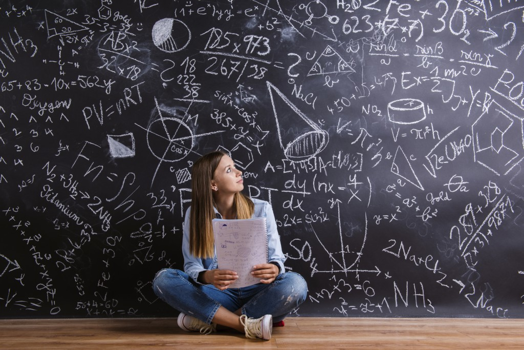 Beautiful young girl in front of blackboard