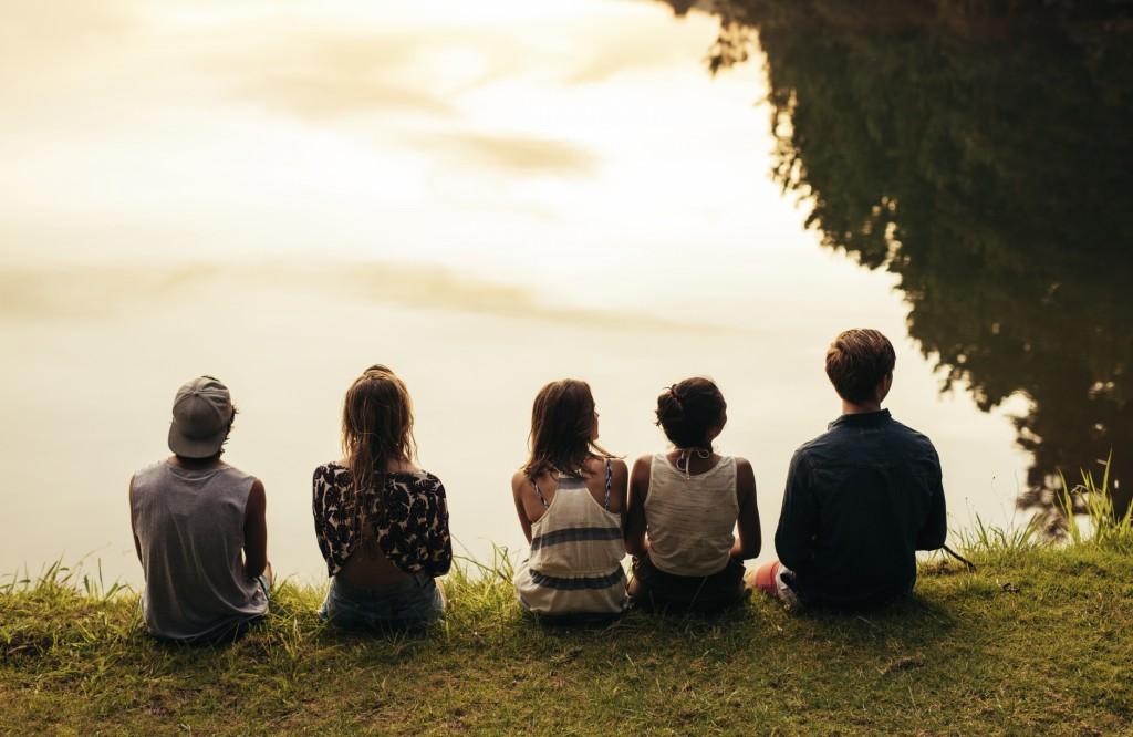 kids sitting by lake