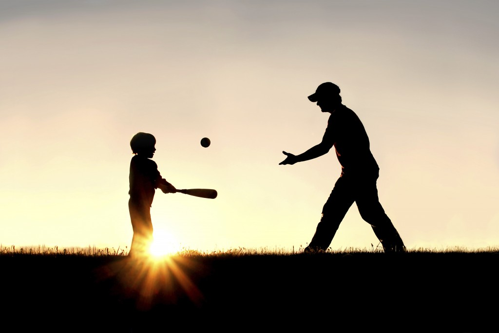 father and son playing catch in the sunset