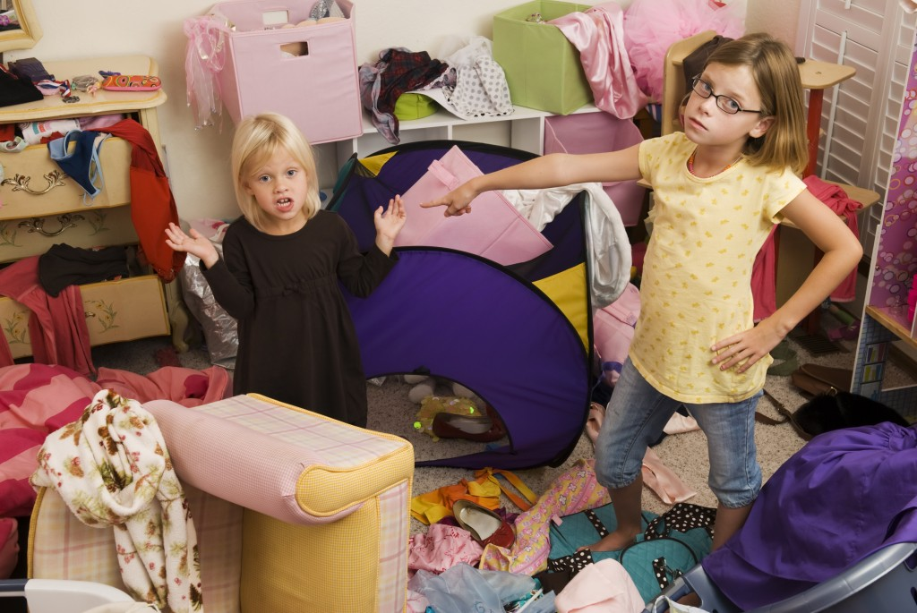 One little girl pointing at another girl in messy room-Series
