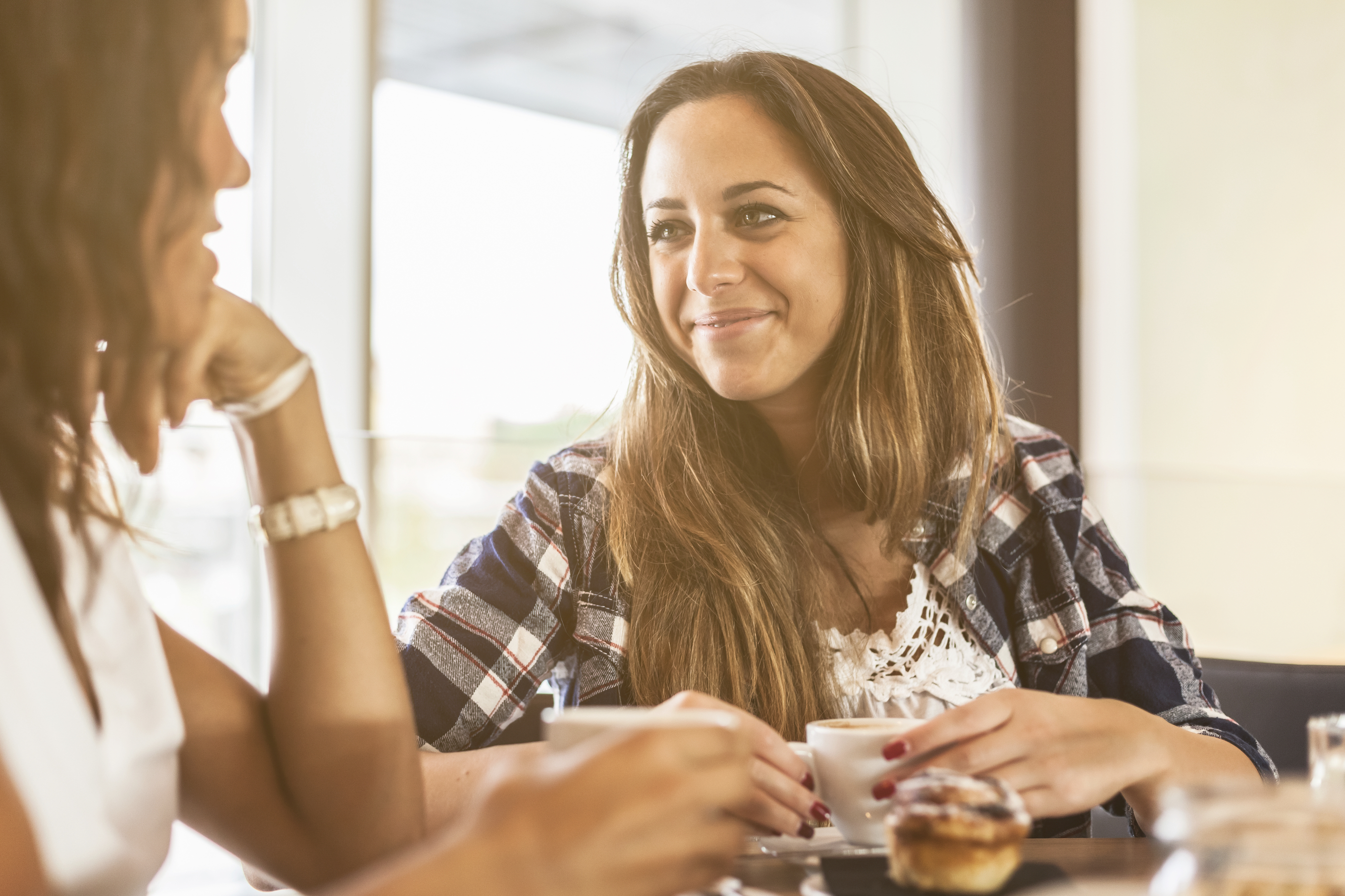 Two young and beautiful women meet at the bar for a cappuccino and to chat. A woman looks smiling and supports the chin with his hand, the other looks at her and smiles