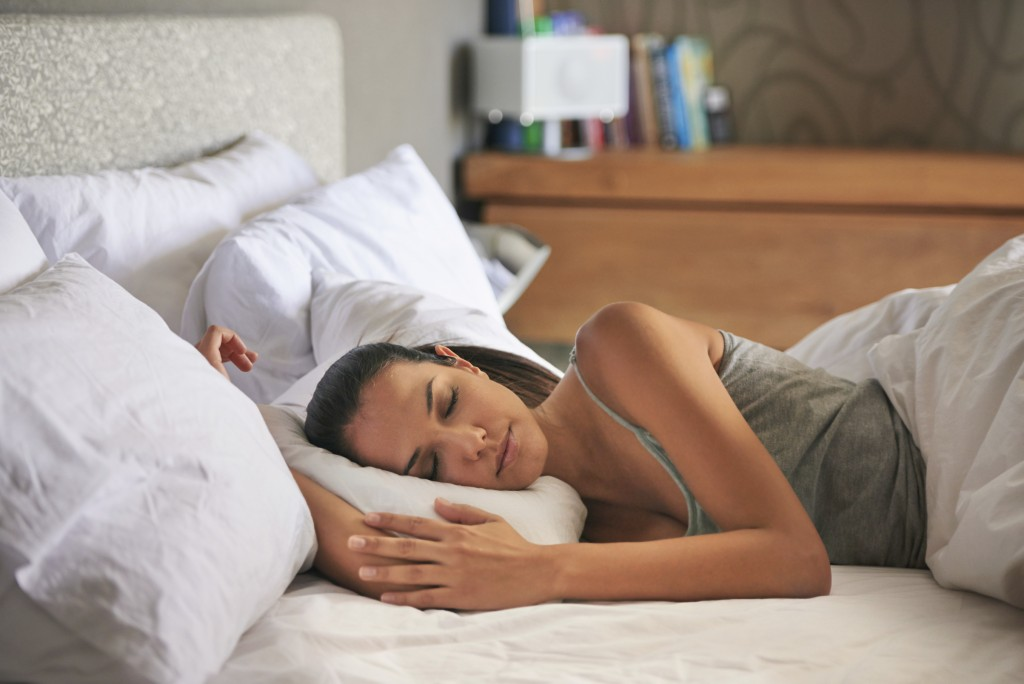 Attractive young woman peacefully sleeping in her bedroom