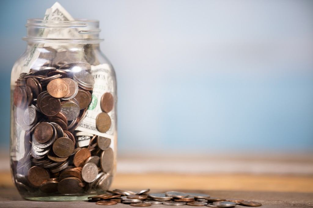Money jar with U.S. currency.  Savings, donations concepts.