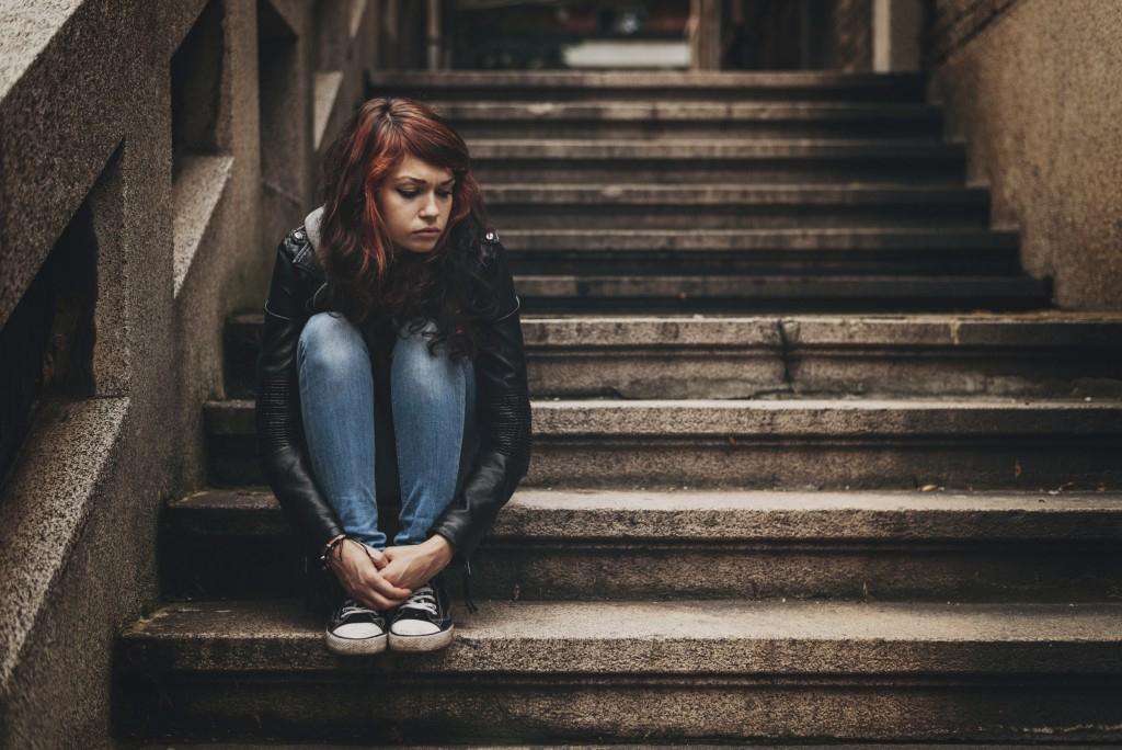 Lonely teenager sitting on stairs with copy space