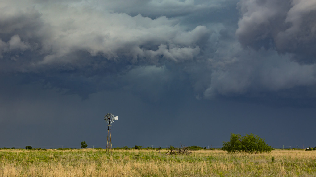 Close-up old-style windmill dwarfed by severe, threatening thunderstorm