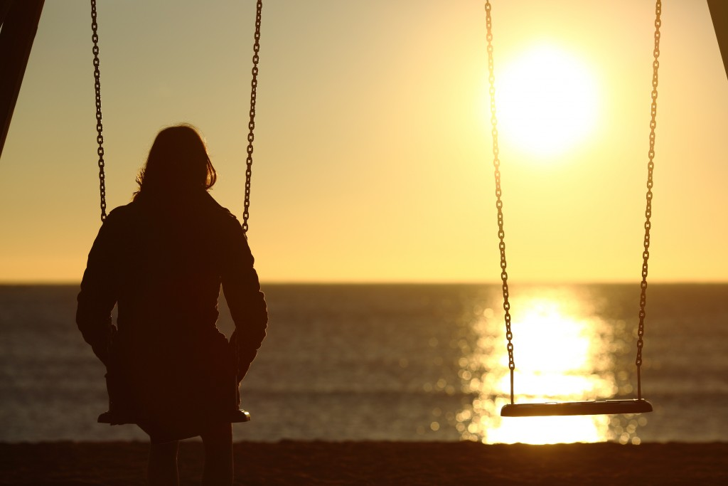 Lonely woman watching sunset alone in winter on the beach at sunset