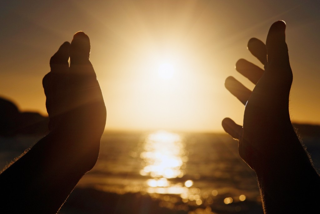 Hands seen in silhouette outstretched towards the setting sun. Copy space on the sun and sky.