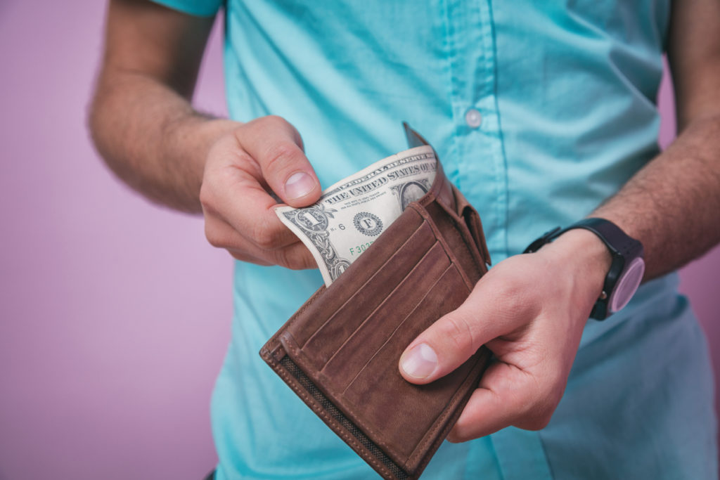 man holding wallet with a $1 bill sticking out