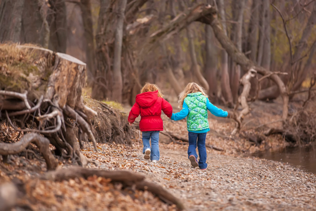Rear view of two young girls (sisters) walking along the bank of the Mississippi River on an autumn day. The younger sister has curly red hair and is wearing a red jacket with her blue jeans. Her older sister has curly blonde hair and is waering a green vest over a turquoise blue fleece shirt. The girls are holding hands as they walk along the riverbank.