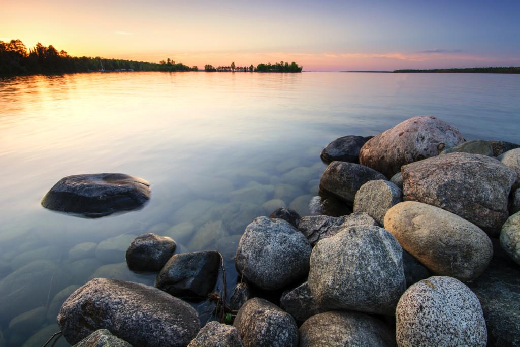 Large boulders on lake shore at sunset. Minnesota, USA
