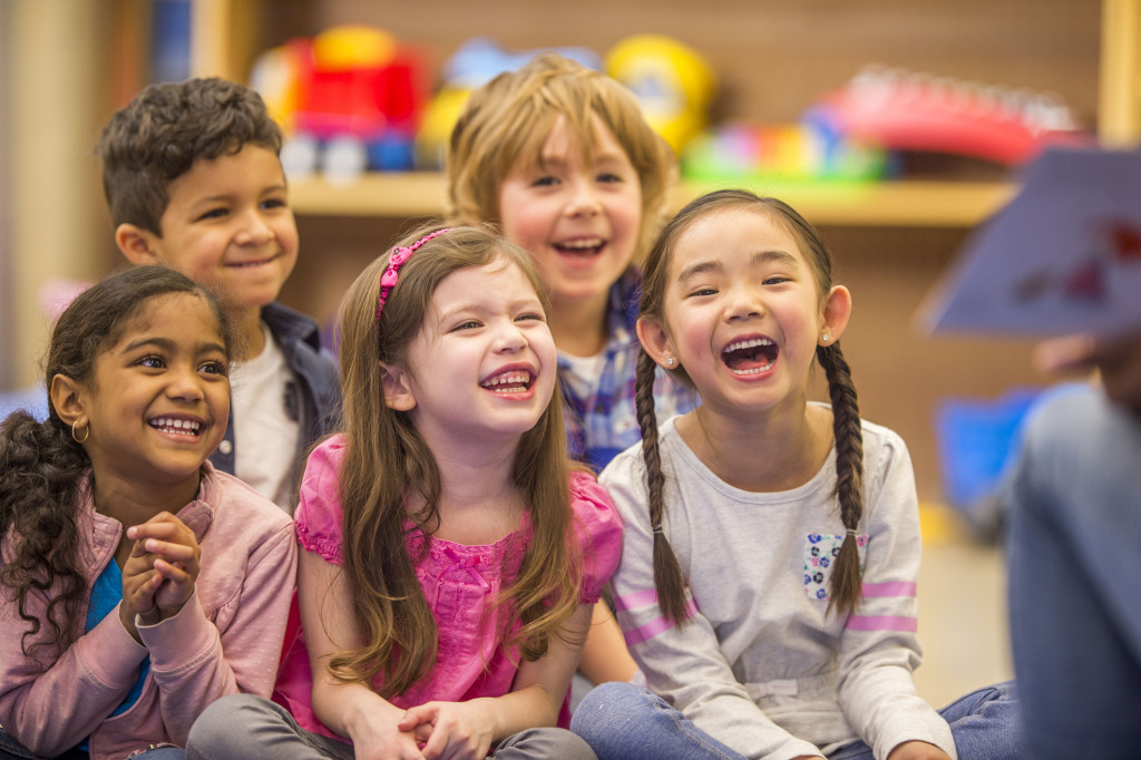 A multi-ethnic group of elementary age children are laughing while their teacher reads them a book during story time.