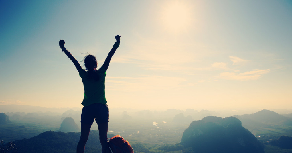 silhouette of cheering woman hiker open arms at mountain peak