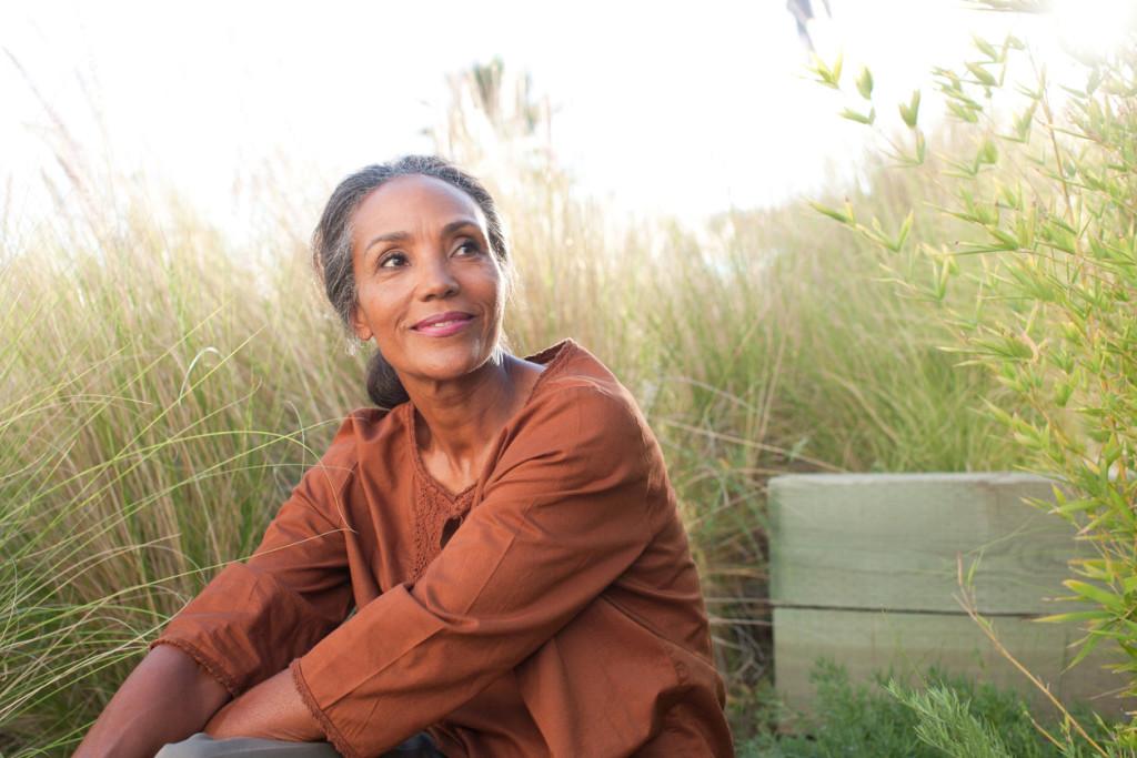 Serene woman sitting in sunny field