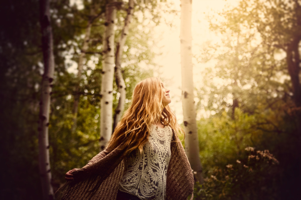 A beautiful young woman with a joyful expression of peace in a forest nature scenic. She has long golden hair, and is looking up and away toward hazy sunshine shining through the trees.