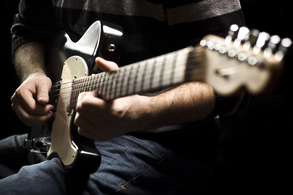 A man plays an electric guitar