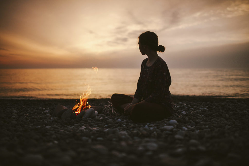 Girl sitting near the fireplace on the beach