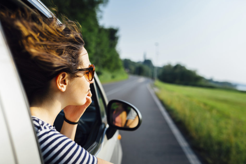 girl with her hair blowing in the wind traveling by car.