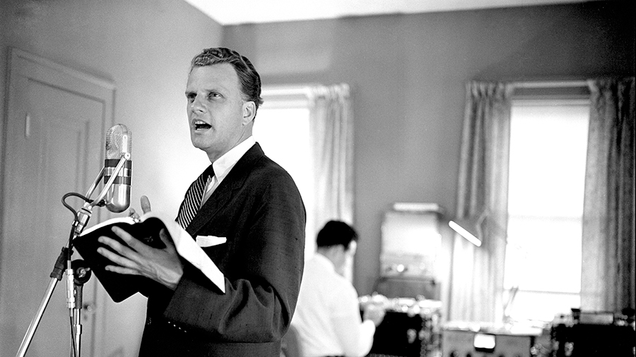 Dr. Billy Graham standing behind a microphone, holding a Bible, circa early 1950s